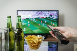 someone holding a remote watching sports